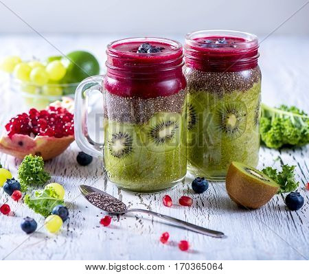 Green and red smoothie vitamins diet drink with kale chia seeds lime kiwi apple pomegranate