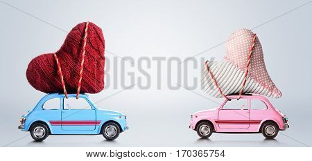 Couple of retro toy cars delivering craft hearts for Valentine's day on gray background