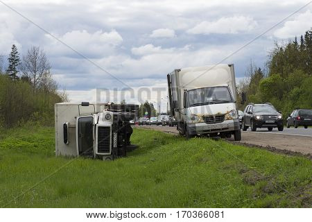 LENINGRAD REGION, RUSSIA - MAY 17, 2015: Inverted cargo van-refrigerated truck lies in a ditch
