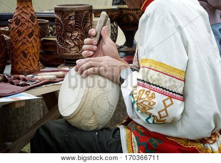The revival of the ancient craft: man in national costume is decorated with carved wooden dishes with the help of special tools.