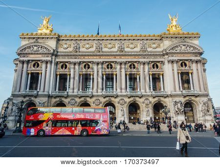 PARIS, FRANCE - CIRCA DECEMBER 2016: A City Sightseeing bus in front of the Palais Garnier. The Palais Garnier is an opera house, which was built from 1861 to 1875.