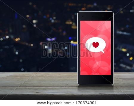 Love message on modern smartphone screen on wooden table over blur colourful night light city tower Internet online connection Valentines day concept