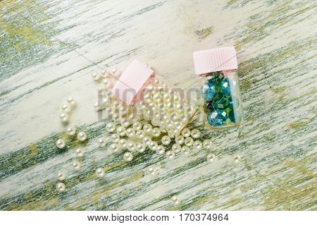 Scattered Pearl Beads And Jars Filled With Pearls And Blue Beads.