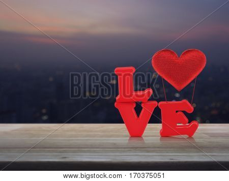 Red love alphabet and fabric heart on wooden table over blur aerial view of cityscape on warm light sundown Valentines day concept