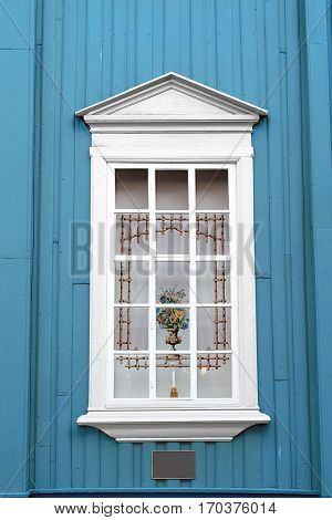 blue wall white window curtain vase candle holder
