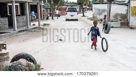 Zanzibar, Tanzania - July 14, 2016: Children in Zanzibar, Tanzania playing with tires outside, vehicles on the background