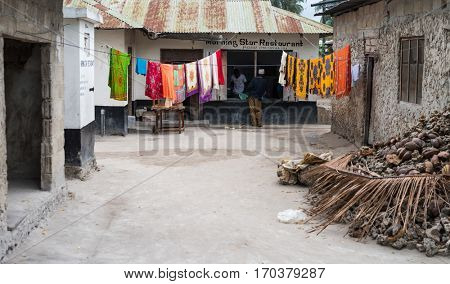 Zanzibar, Tanzania - July 14, 2016: Clothing hanging outside in Zanzibar, shacks where local people live and a restaurant