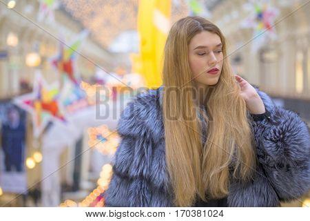 Young beautiful blonde girl in fur blue coat posing in the shop
