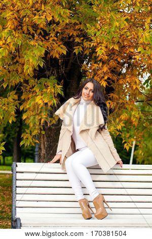 Beautiful arabic brunette women in white sheepskin coat sitting on a bench in the autumn park