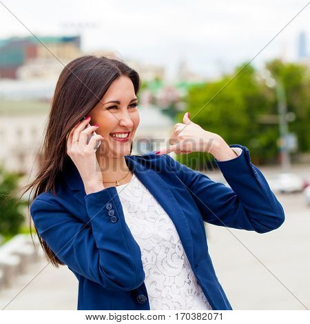 Beautiful brunette woman making a call me gesture, summer outdoors
