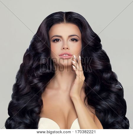 Spa Model Pretty Woman with Healthy Skin and Long Wavy Hair. Beautiful Permed Hairstyle and Natural Nude Makeup