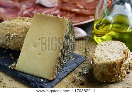 closeup of a piece of manchego cheese, some slices of bread, a cruet with olive oil and a plate with an assortment of different spanish cold meats as chorizo, cured pork tenderloin and serrano ham
