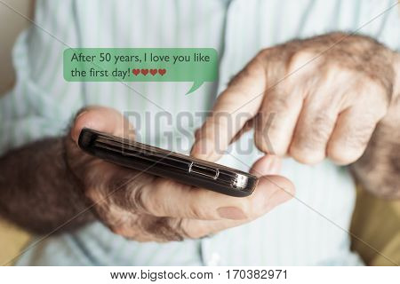 closeup of an old caucasian man sending or reading a text message in his smartphone with the text after 50 years I love you like the first day
