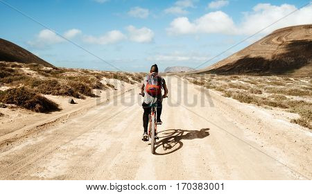 a young caucasian man seen from behind riding a bike in a dirty road in La Graciosa, Canary Islands, Spain