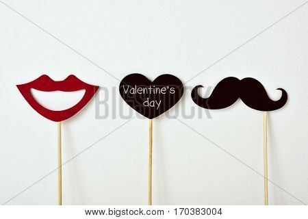 a mouth, a mustache and a heart-shaped signboard with the text valentines day, attached to some sticks, against an off-white background