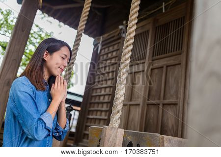Woman wishes blessing in Japanese temple
