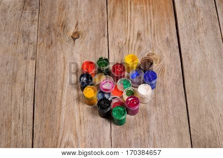 Paint And Brushes Depicting The Heart On The Wooden Background