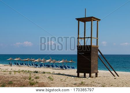 Lifeguard tower with empty loungers on the beach