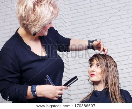 Women's haircut. Hairdresser, beauty salon. Professional hairdresser making stylish haircut. Happy hairdresser cutting woman long hair. Young beautiful woman having her hair cut at the hairdresser's