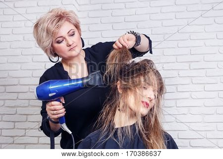 Professional hairdresser drying hair for client. Stylist holding a hairdryer in the hand. Hairdresser making hot styling. Hair drying process at salon