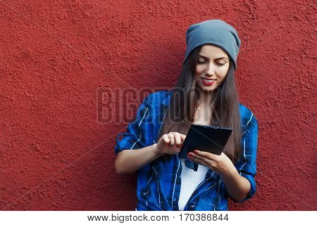 Portrait of a cheerful hipster woman holding tablet computer. Young hipster smiling girl using digital tablet outdoors, red wall in the background with copy space, social networking concept