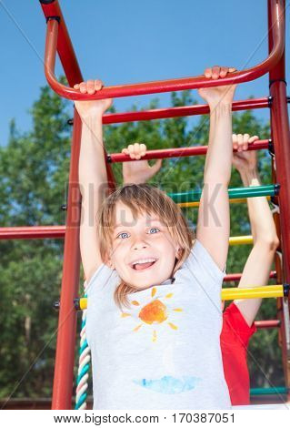 Low angle view of happy girl wearing hanging from a climbing frame in a playground looking at camera smiling enjoying summertime