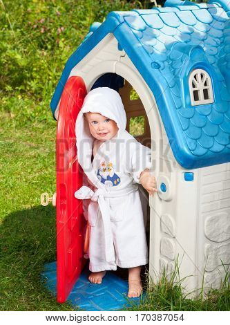 Little baby girl wearing white bathrobe looking out from plastic play house doorway in a summer playground