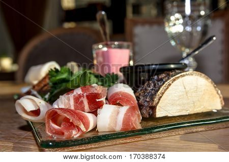 Bacon (salo) With Streaks Of Meat With Onion And Parsley Lying On A Glass Plate. As Decoration Used