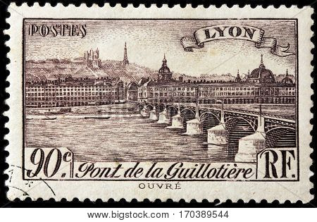LUGA RUSSIA - FEBRUARY 7 2017: A stamp printed by FRANCE shows view of the Bridge Guillotiere in Lyon - city in east-central France in the Auvergne-Rhone-Alpes region circa 1939