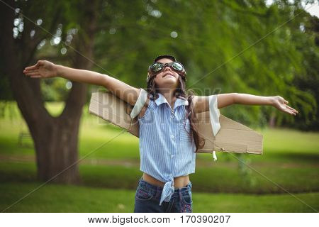 Young girl wearing leather pilot helmet and wings pretending to fly in garden