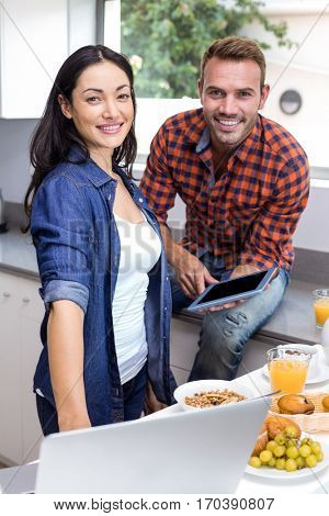 Portrait of couple using laptop and digital tablet in the kitchen
