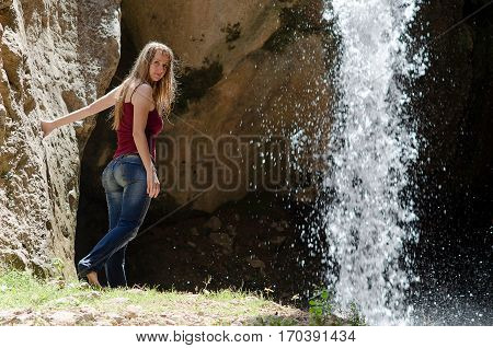 Young woman in wet jeans staying near waterfall in Tien-Shan mountains, Uzbekistan