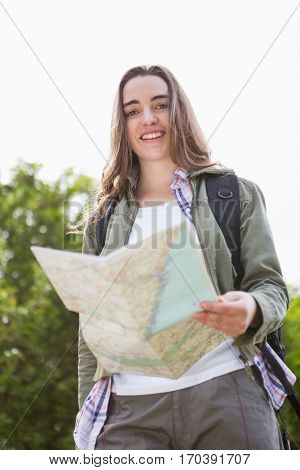 Smiling woman checking the map in the countryside