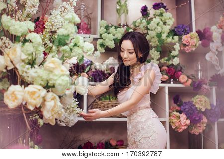 Beautiful girl in tender pink dress standing against floral background in flower shop. Joyful asian female florist. Playful fashion model looking and touching many spring flowers.