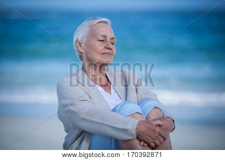 Thoughtful mature woman day dreaming on the beach
