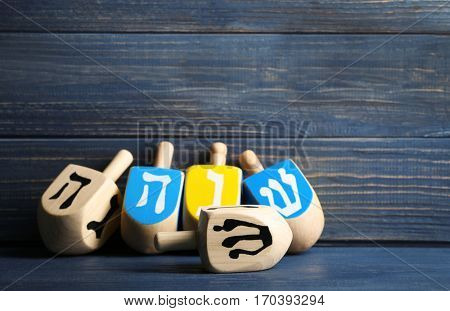 Dreidels for Hanukkah on table against wooden background