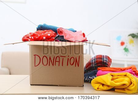 Donation box with clothing on table