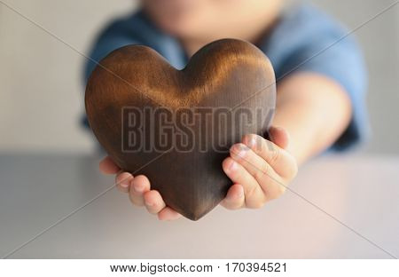 Child holding brown wooden heart, closeup. Adoption concept