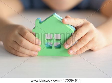 Child holding figures in shape of houses, closeup. Adoption concept