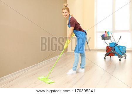 Pretty adult woman moping floor in corridor