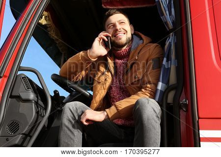 Driver talking by mobile phone while sitting in cabin of big modern truck