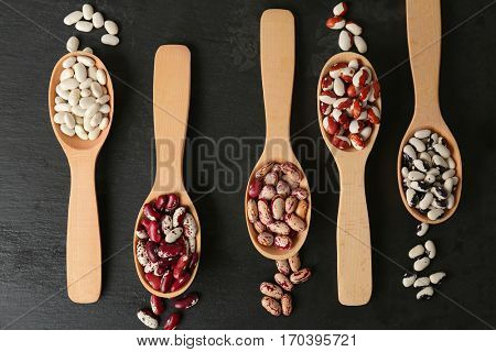 Assortment of haricot beans in spoons on black wooden background