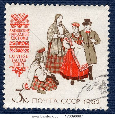 USSR - CIRCA 1962: Postage stamp printed in USSR shows image of musicians and dancers latvian in traditional and historic regional costumes, from the series
