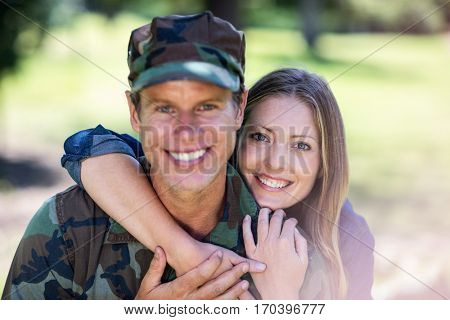 Portrait of happy soldier reunited with his partner in the park on a sunny day