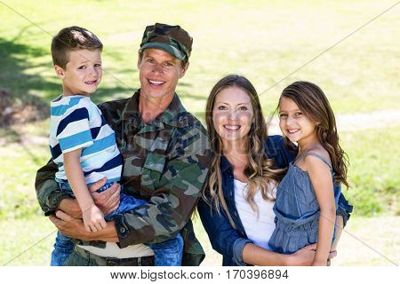 Soldier reunited with his family in the park on a sunny day