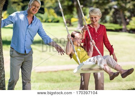 Grandparents pushing their granddaughter on swing in park