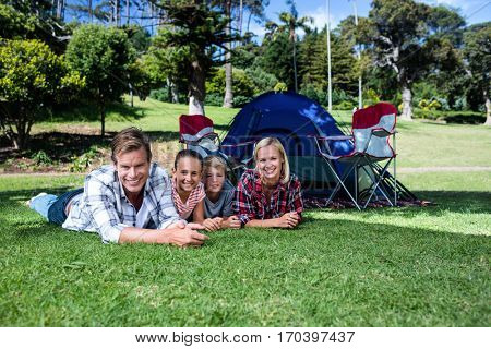 Portrait of happy family lying on grass outside the tent