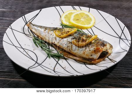 Grilled mackerel fish with lemon and rosemary on white plate