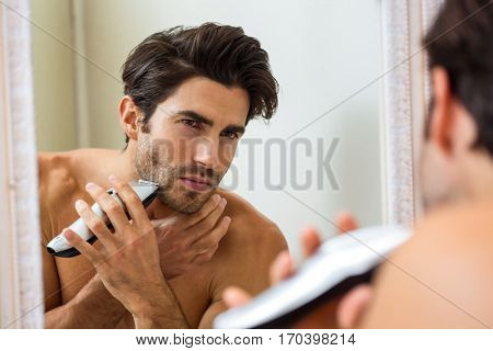 Reflection of young man shaving with trimmer in front of mirror