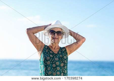 Senior woman posing with sunhat at the beach
